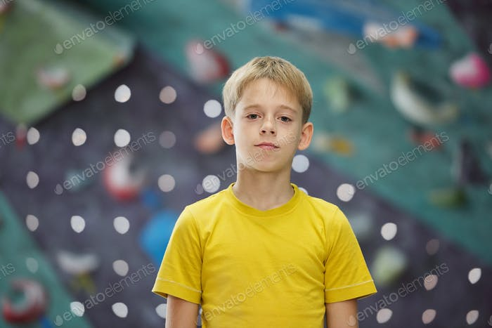 Active boy of elementary age standing in front of camera while standing in gym