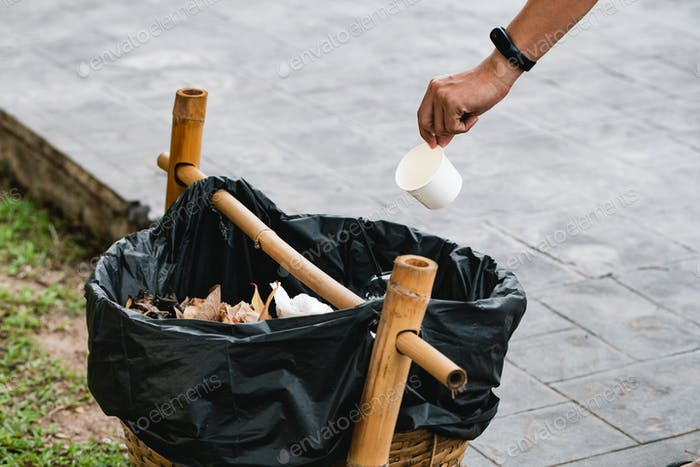 The man throwing paper cup in litter bin outdoors. Recycling concept on a sunny day against the