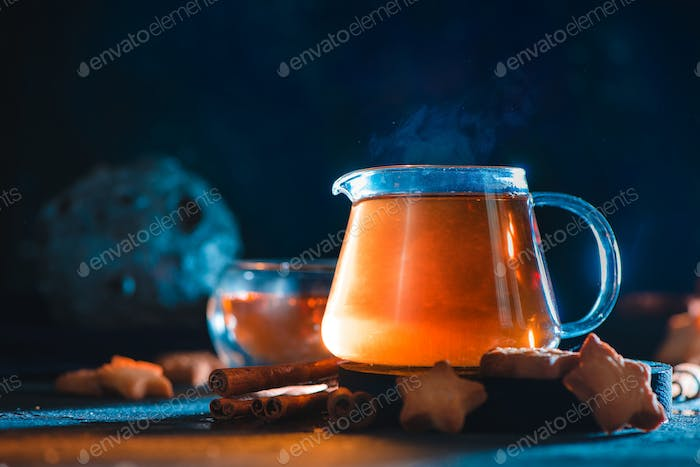 Star cookies with glass teapot on a dark background with a meteorite. Creative food photography with