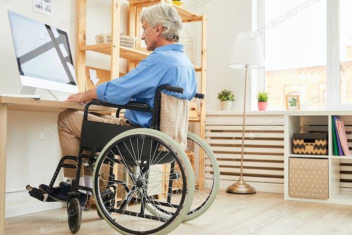 Disabled man using computer at home