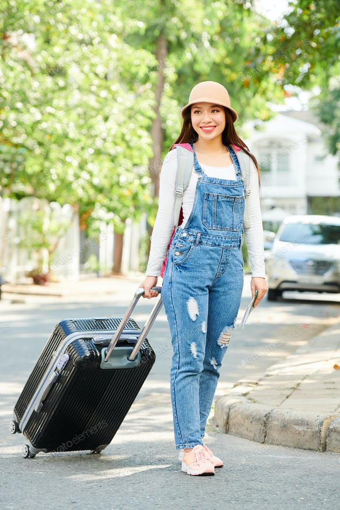 Cheerful female traveler with big suitcase