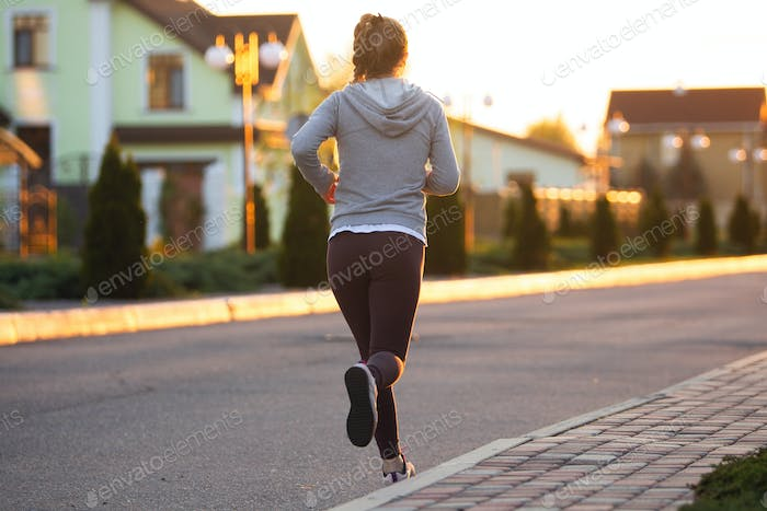 Young female runner, athlete is jogging in the city street in sunshine. Beautiful caucasian woman