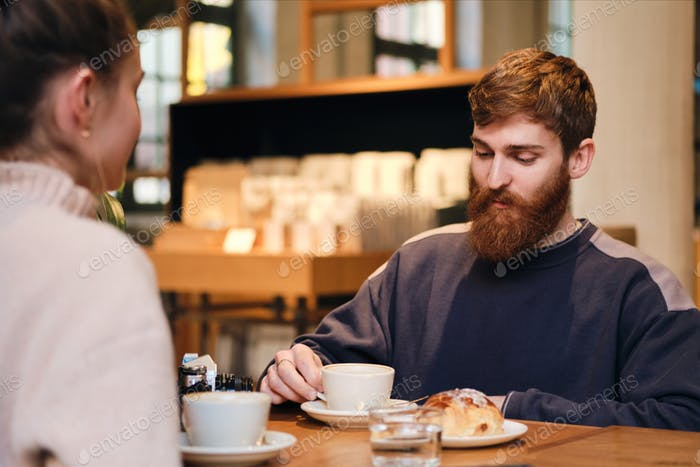 Young attractive bearded man drinking coffee resting with girlfriend in cafe