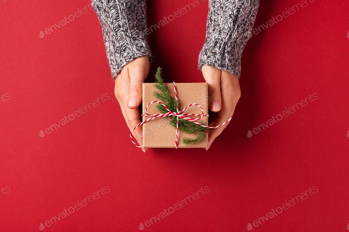 Female`s Hand in Gray Pullover Holding Christmas Gift Box.