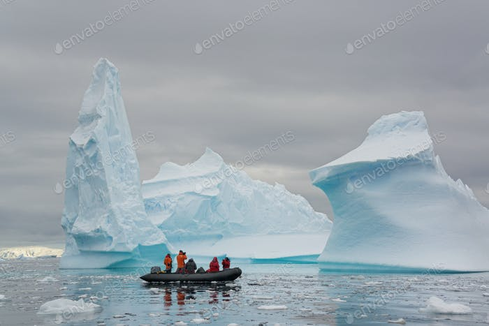 People in zodiac rib boats passing towering sculpted icebergs in Antarctica