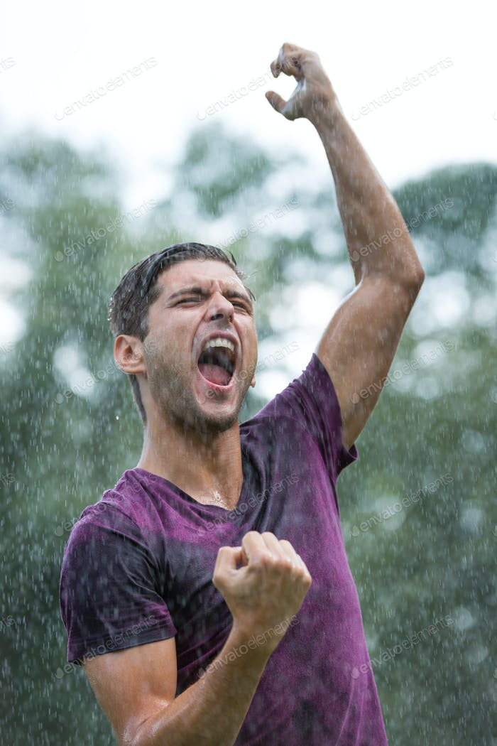 Excited man in summer rain