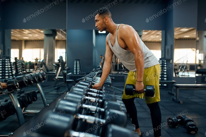 Muscular man choosing heavy dumbbells in gym