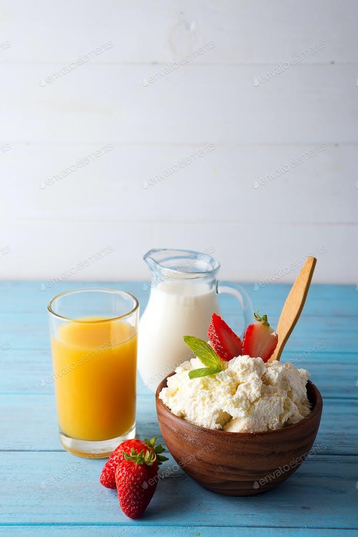 Hüttenkäse zum Frühstück mit Erdbeeren, Milch und Saft auf blauem Holzhintergrund