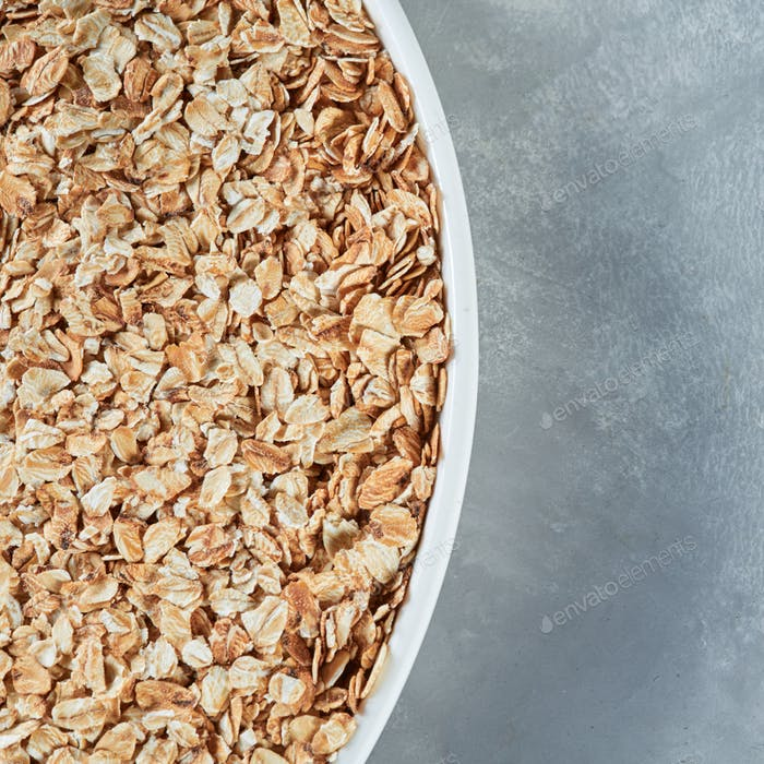 Uncooked oat flakes in a white bowl on a gray background. Close up, top view of natural organic