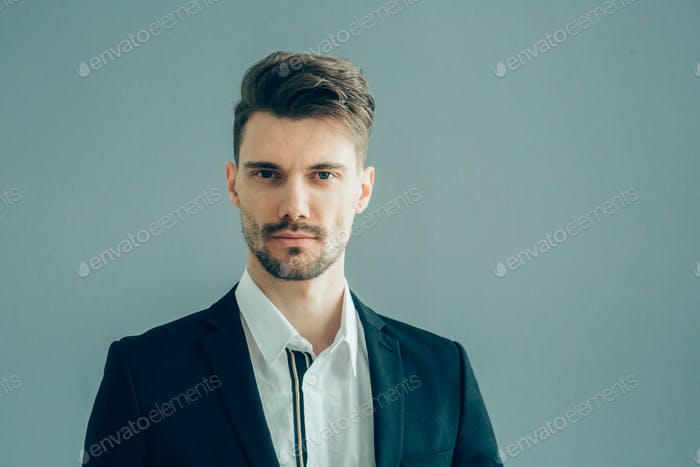 Handsome man in suitover gray wall. Businessman male portrait fashion style guy