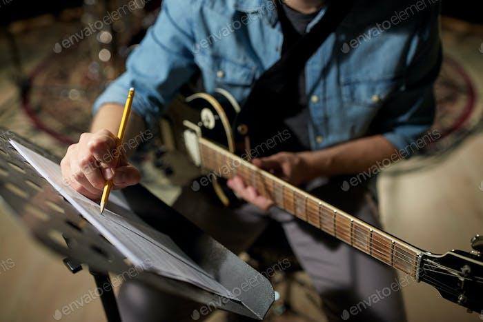 Mann mit Gitarre schreiben Musikbuch im Studio