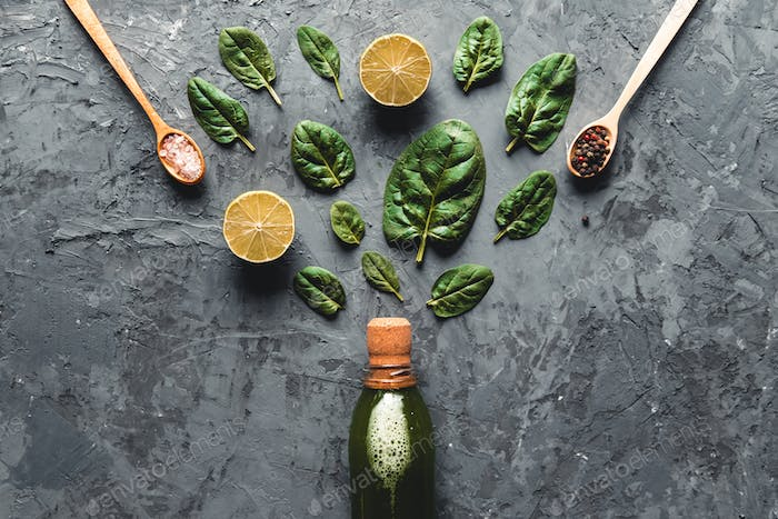Spinach and lemon smoothie in the bottle. Fresh spinach in wooden plates. Useful food, eco, vegan