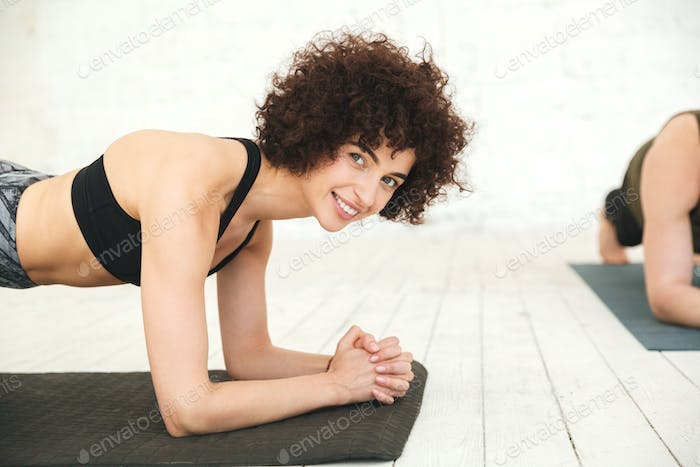 Smiling fitness woman planking on an exercise mat