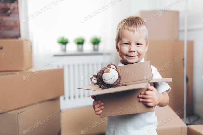 Lindo niño ayudando a las cajas de embalaje