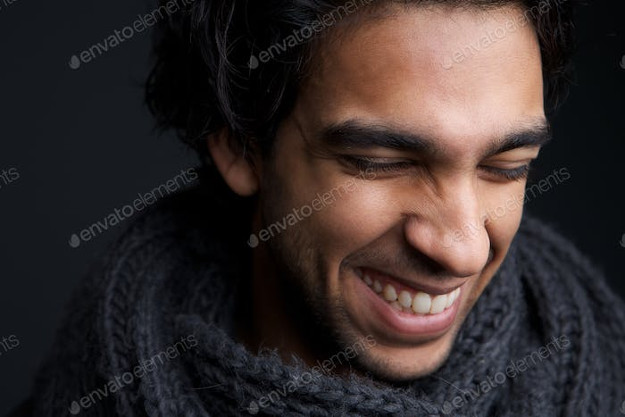 Young man laughing with gray scarf