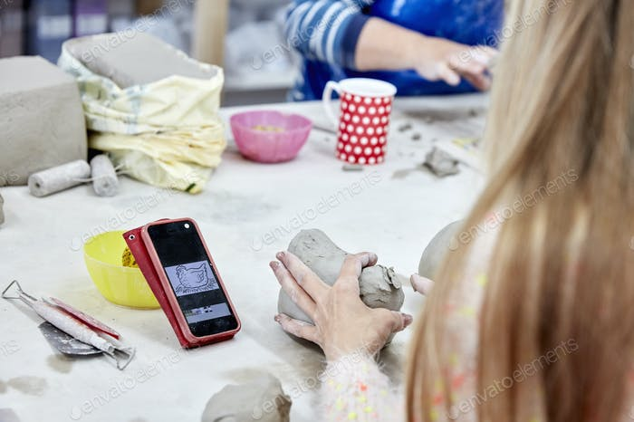 Gente sentada en un banco de trabajo en un estudio de cerámica. Una mujer usando un boceto en su teléfono como referencia
