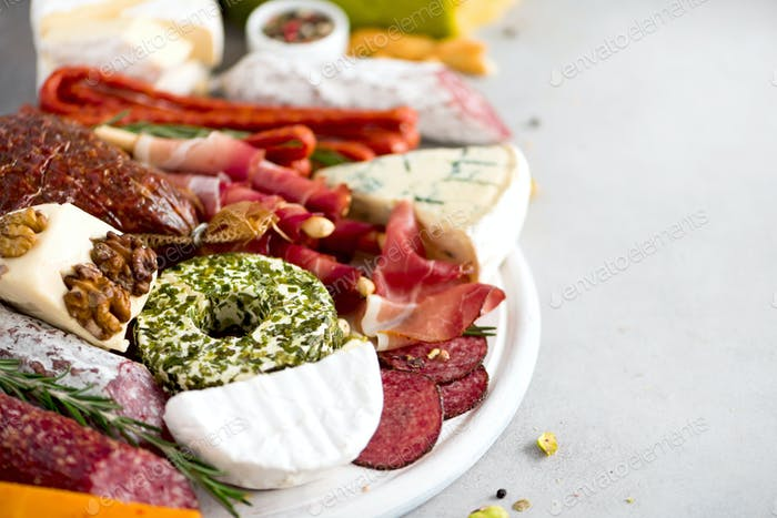 Cheese and meat appetizer. Traditional italian antipasto. Cutting board with salami, cold smoked
