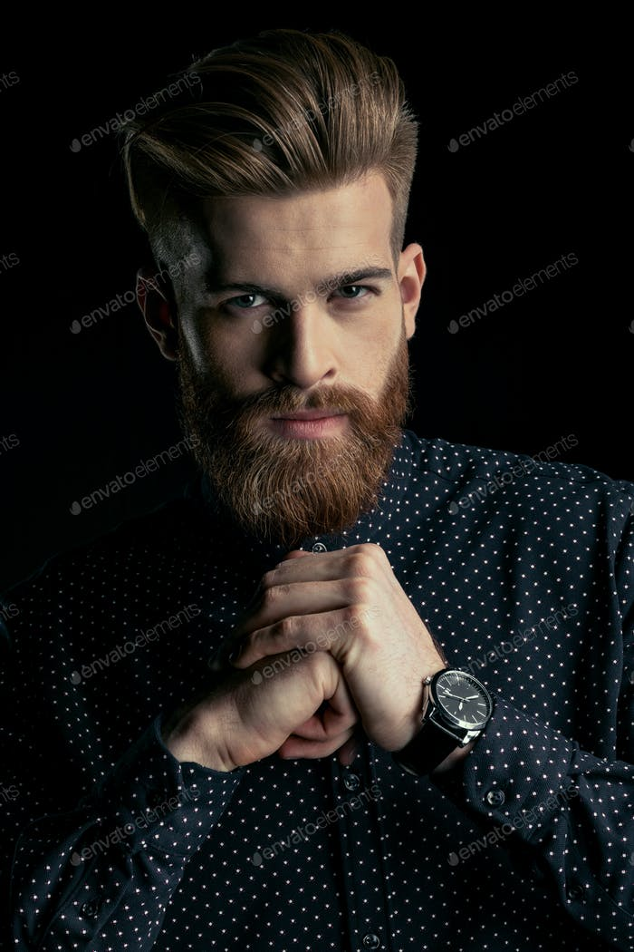 Handsome stylish bearded man with wristwatch looking at camera