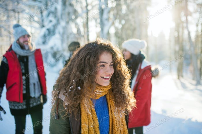 A portrait of young woman with friends standing outdoors in snowy winter forest.