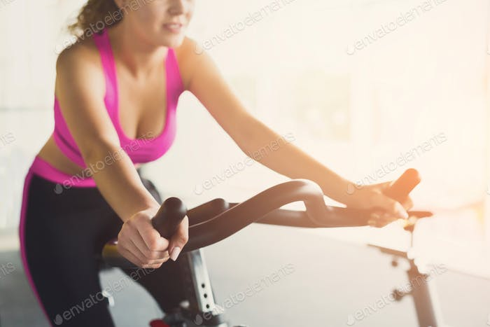 Woman in gym on exercise bikes