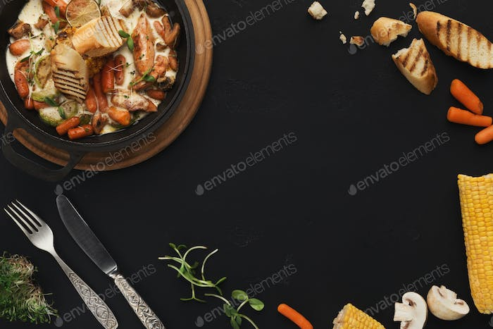 Meat and vegetable ragout on black table, top view