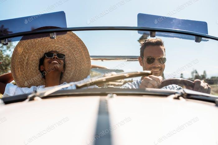 Multiracial Paar in einem Cabrio Oldtimer