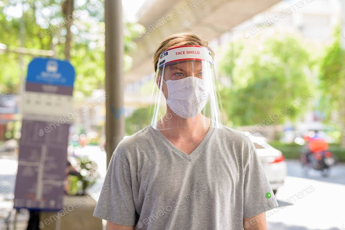 Young man with mask and face shield for protection from corona virus outbreak waiting at the bus