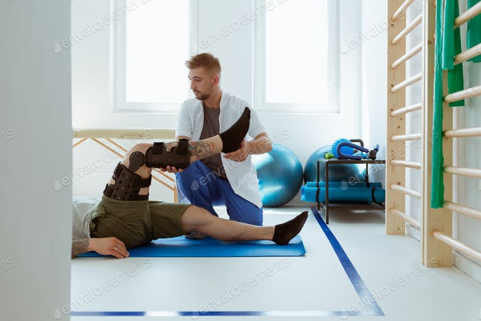 Young physiotherapist exercises in a bright medical office with his injured patient