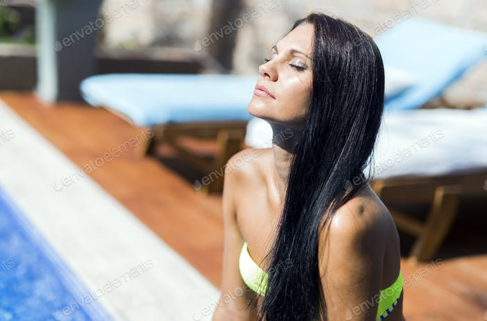 Beautiful woman with closed eyes sunbathing