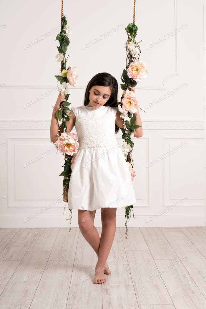 Young girl sitting on swing in spacious room