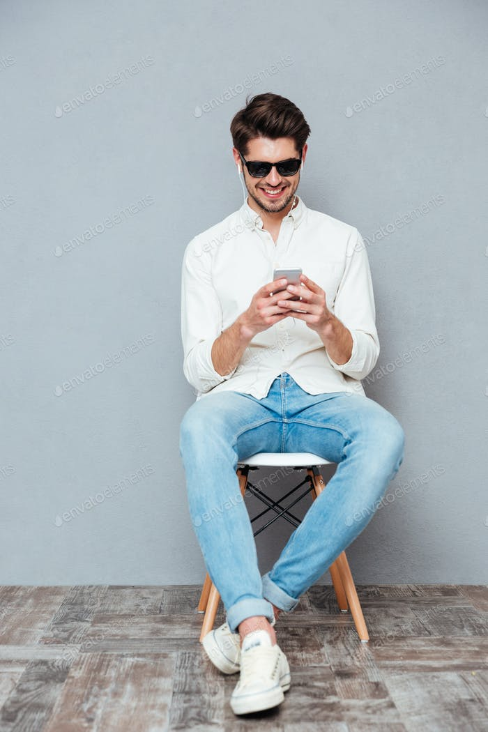 Happy young man in sunglasses listening to music from smartphone