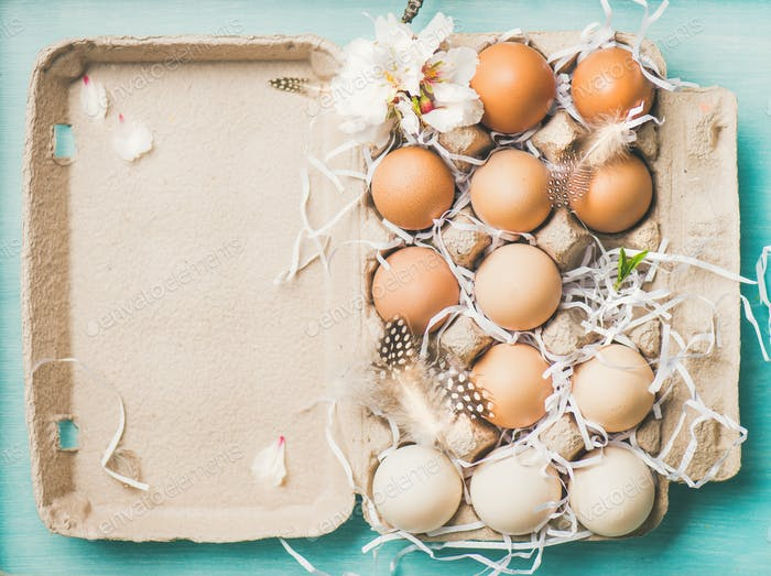 Natural colored eggs for Easter in box, blue background