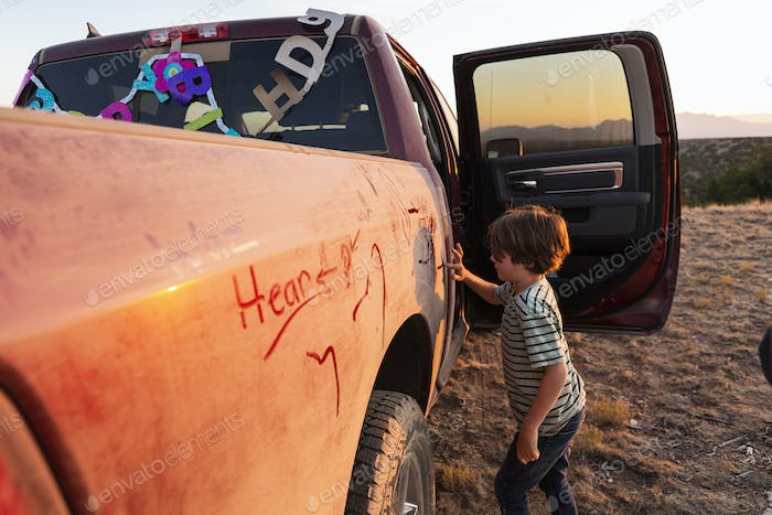 young boy writing on dirty pickup truck