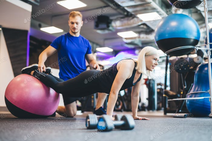 Woman working out on a ball with personal trainer.