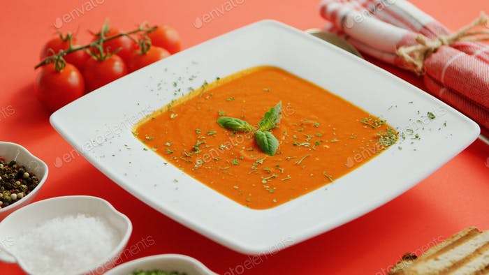 Tomato soup in plate with green leaf