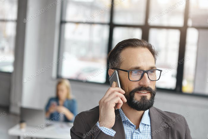 Close up portrait of handsome bearded male enterpreneur in glasses and formal suit discuss current a
