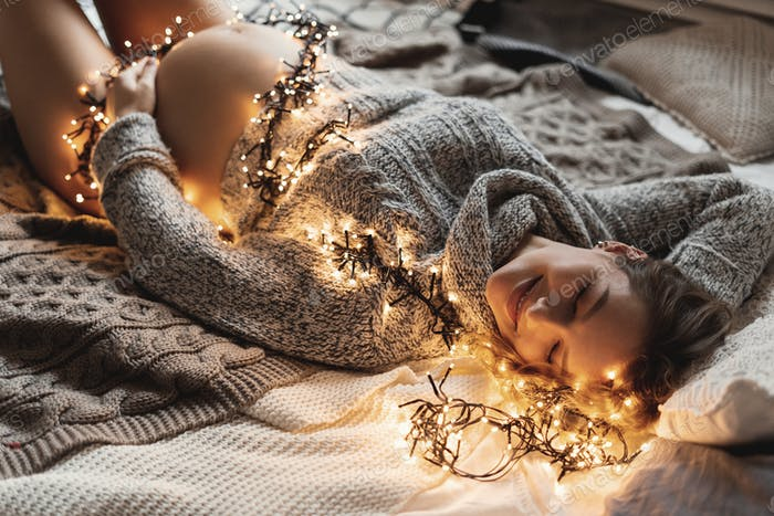 Charming pregnant woman lying on the bed with lights covering he