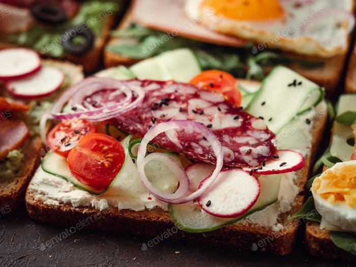 Sandwiches mit Salami, Gemüse und schwarzem Sesam