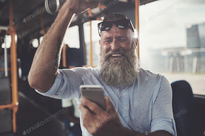 lachend mature man Reiten ein Bus Musik hören