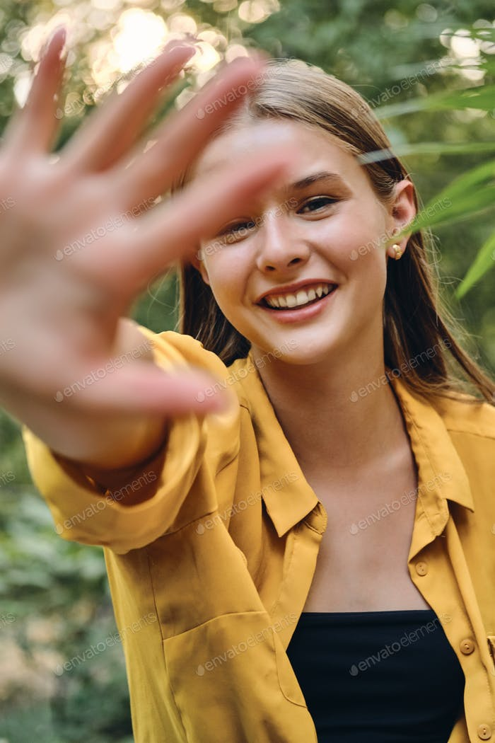 Young beautiful smiling woman in yellow shirt and top happily covering camera with hand in park