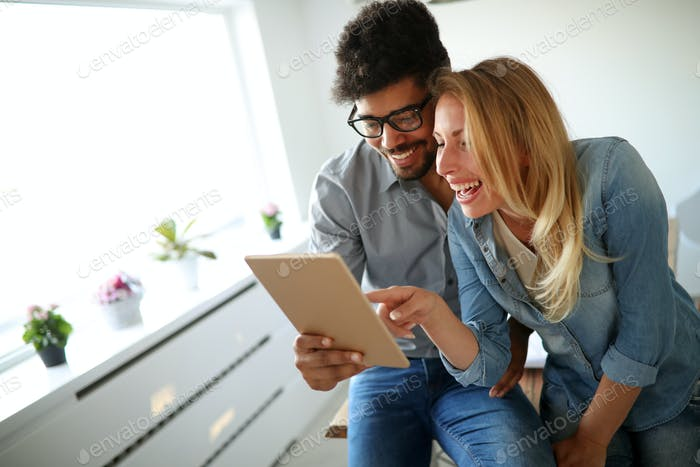 Happy couple in love surfing on tablet at home
