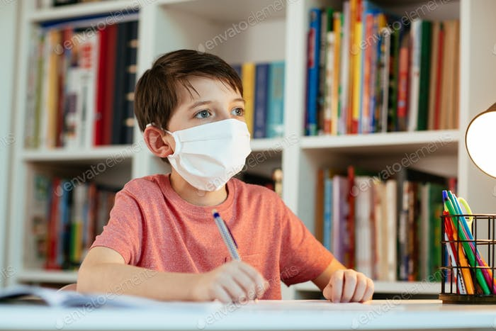 Young student wearing protective mask working in isolation on school assignments.