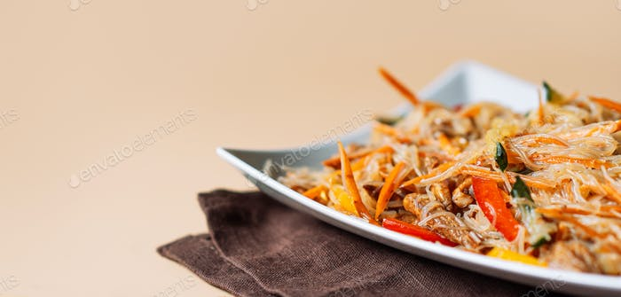 Square plate with spaghetti and meat salad on light background
