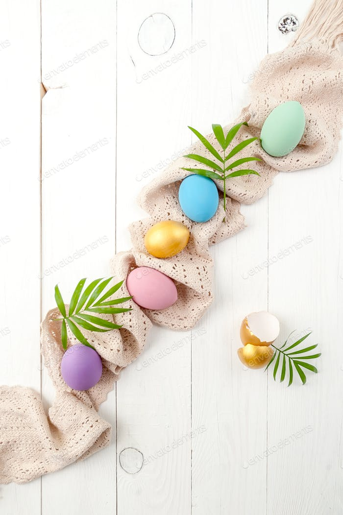 Multicolored easter eggs of pastel and gold color on a white woo