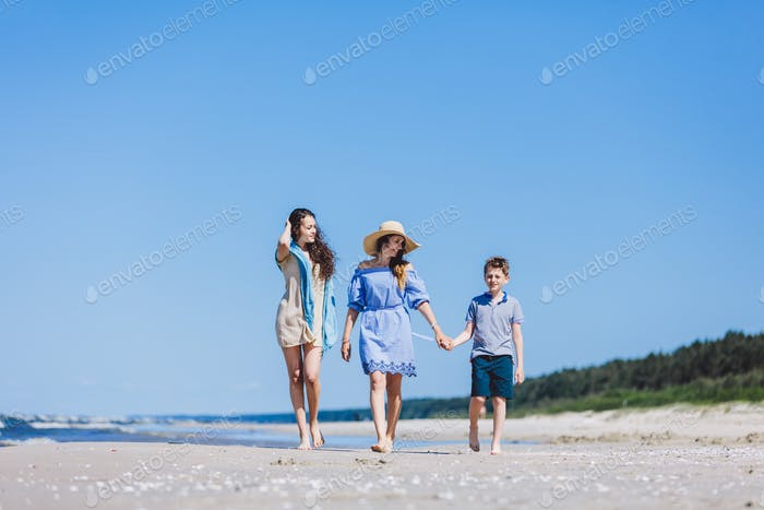 Mother and her two children walking on the beach