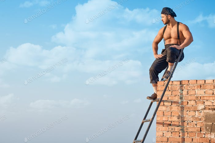 Builder leaning on brick wall on high