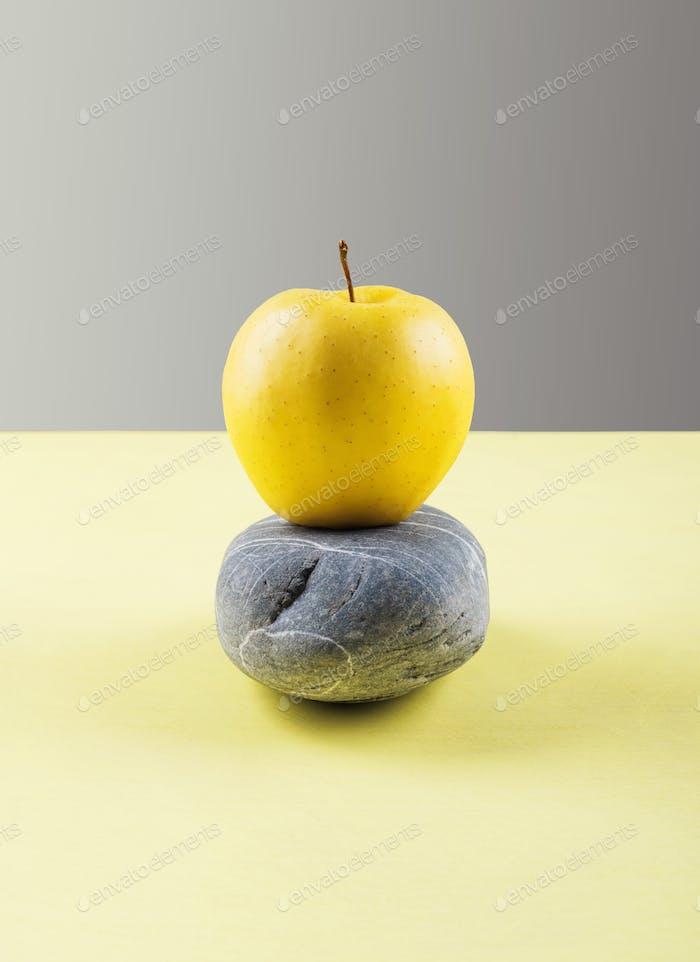 Illuminate yellow apple balance on stone dark gray
