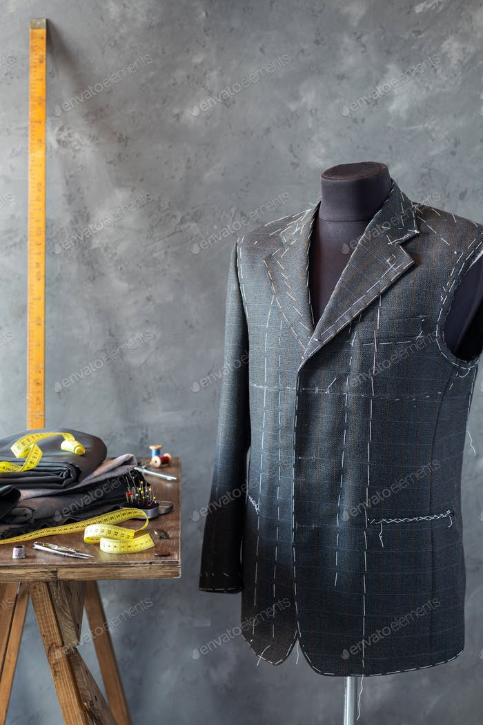 suit jacket on male tailor mannequin and sewing tools,