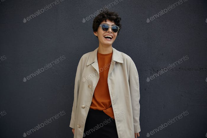 Lifestyle fashion portrait of young stylish hipster woman with short haircut wearing sunglasses