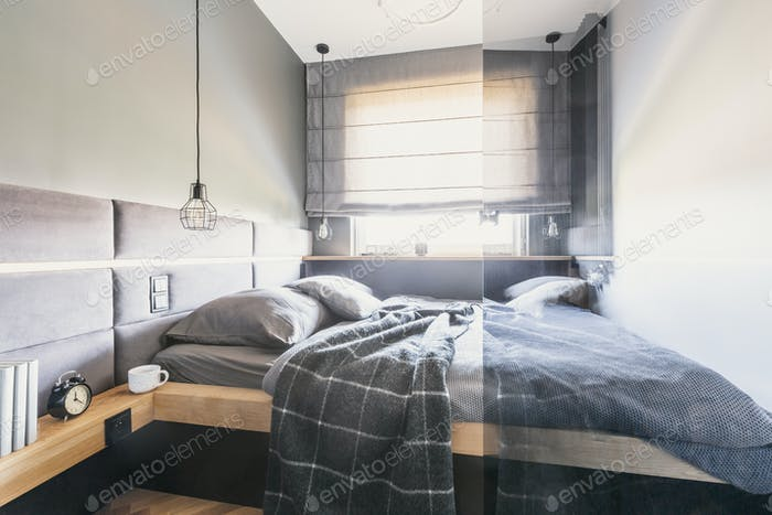 Patterned blanket on bed in grey bright bedroom interior with wi